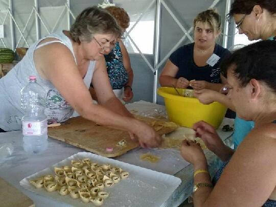 Cuoche al lavoro con la ricotta donata per la produzione di tortelloni