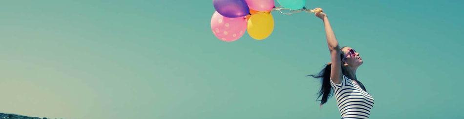 junges Mädchen hält bunte Luftballons in Höhe