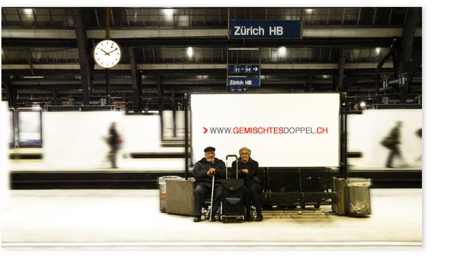 """Ehepaar sitzt auf einer Bank vor Plakat """"Gemischtes Doppel"""" im HB Zürich."""