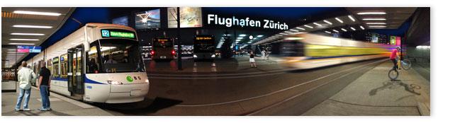 Spannende Nachtscene vor dem Flughafengebäude mit Trams und Passanten.