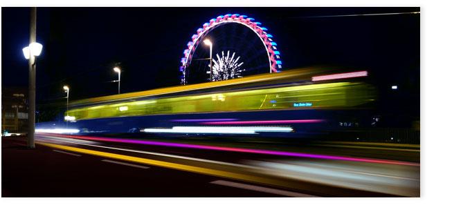 Tram auf Quaibrücke mit Riesenrad im Hintergrund