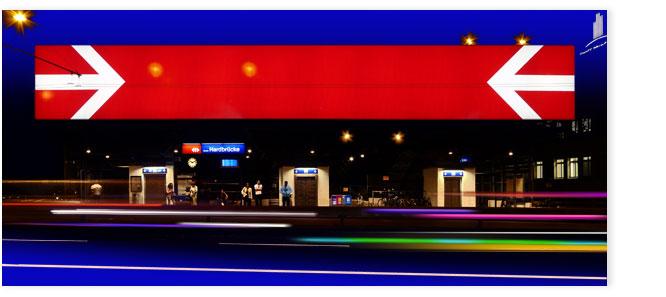 Bushaltestelle Hardbrücke bei Nacht bunt erleuchtet mit grossem SBB Schild.