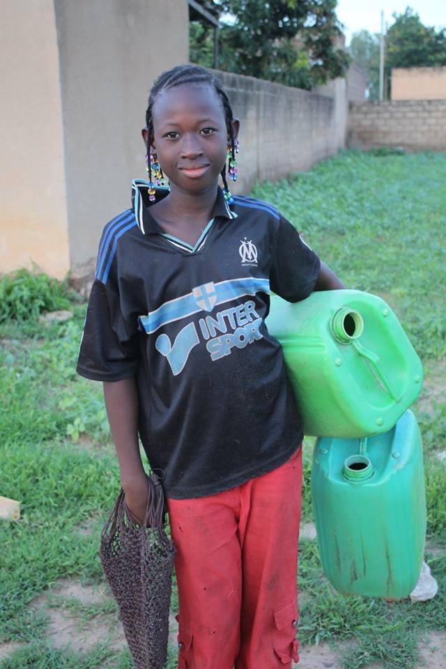 Ein Mädchen mit Kanistern auf dem Weg zum Wasser holen.
