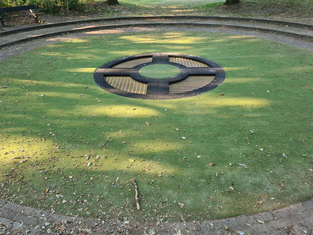 Teppichvlies-Fallschutz auf einem Spielplatz um ein Trampolin