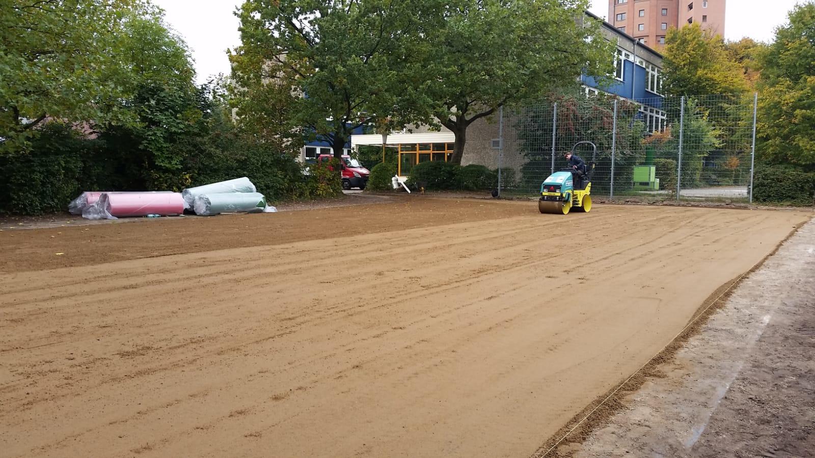 Deckschichteinbau für Teppichvlies-Bolzplatz