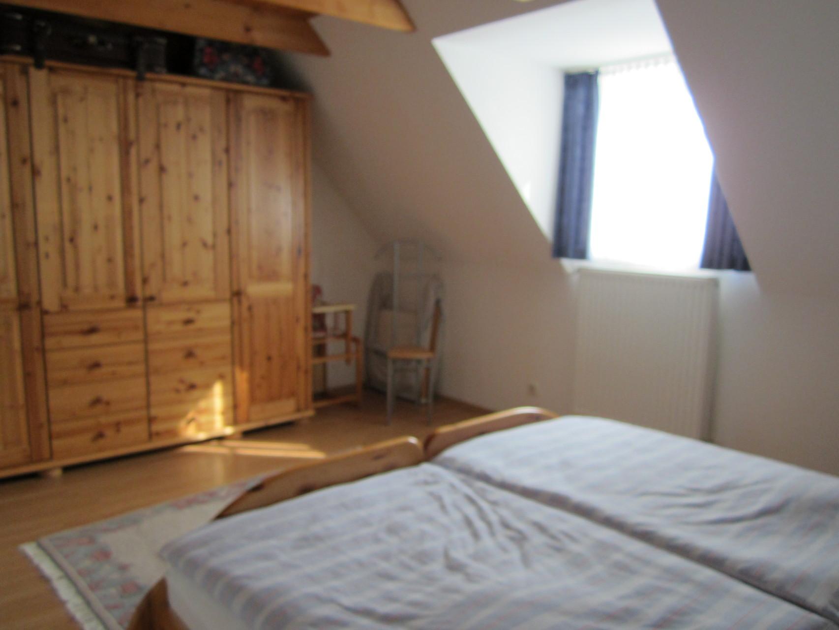 Schlafzimmer mit Doppelbett und Kleiderschrank sowie Platz für's Baby