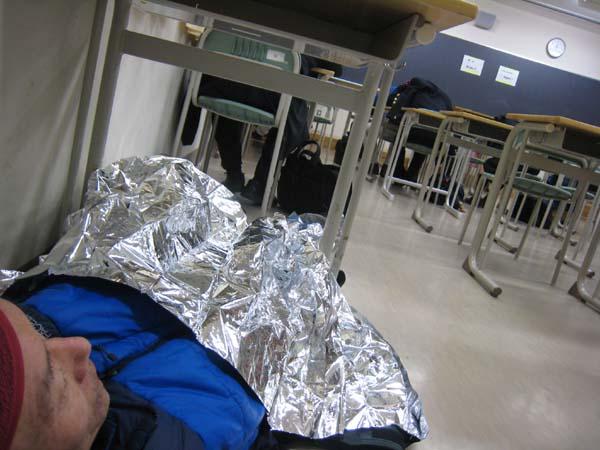 新宿高校でサバイバルシートをかぶって寝る。ちょっとがさがさして迷惑だったかも。  一応暖房はされていたが、明け方はちょっと寒かった。