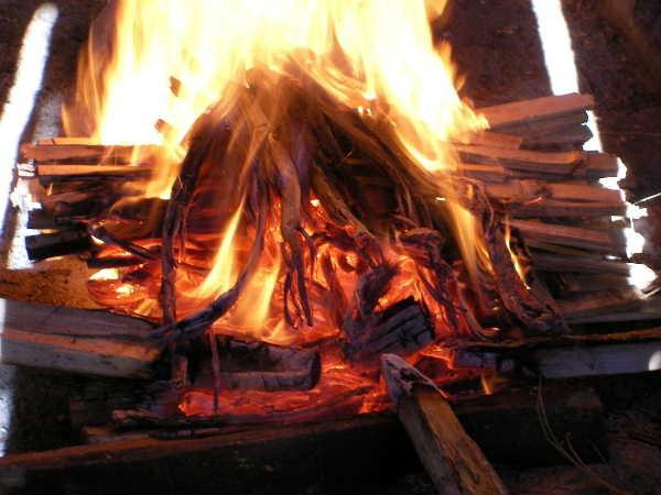 皿を焼くサラヤク族(プッ笑)。後はそのまま燃え尽きるまで待つだけ。はあ~、なんて楽な焼成なんですか。