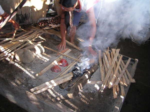 いよいよ焼成開始。器に灰を被せ、竹を井桁に組んでいく。