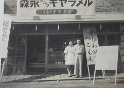 私が生まれる前、父の実家「梅月堂」という菓子店の「臨時店舗」前に立つ父母