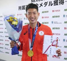 「報奨金 壱億円」と書かれた祝儀袋と花束を手にする見延和靖選手
