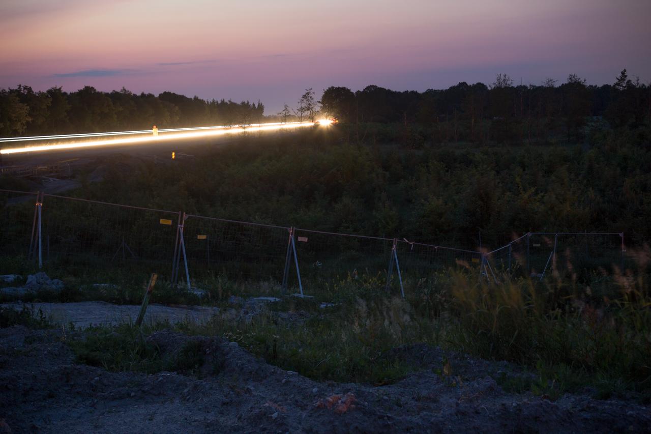 Stetig, selbst in der Nacht, fahren Autos unter der Brücke her und verschwinden in der Ferne.