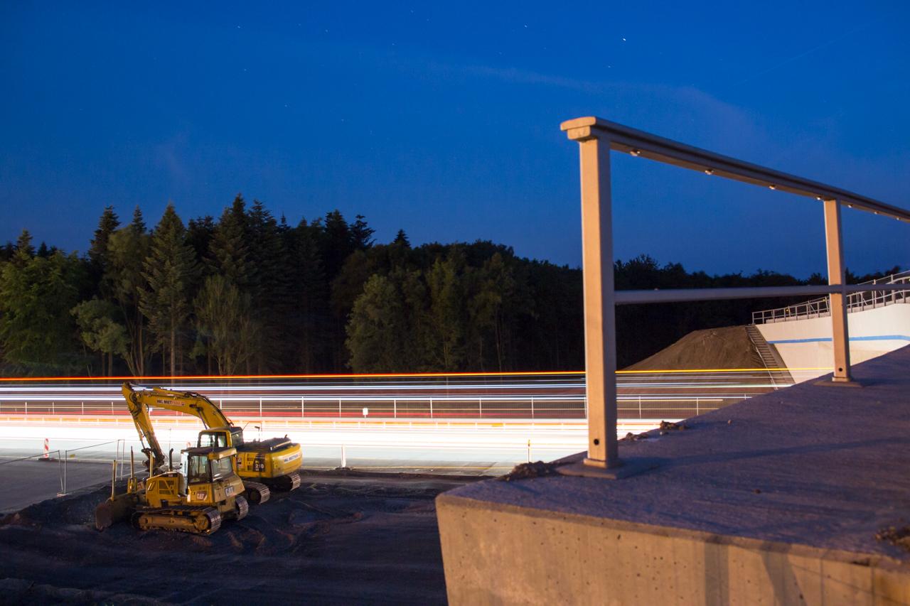 Nachts ruht der Bau, und die Autos erleuchten einen inaktiven Bagger.