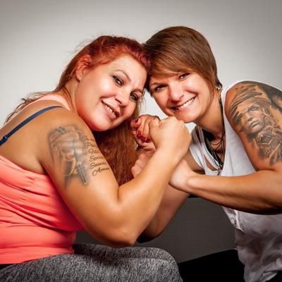 Zwei Frauen lächeln in die Kamera und zeigen dabei ihre kräftigen tätowierten Arme.