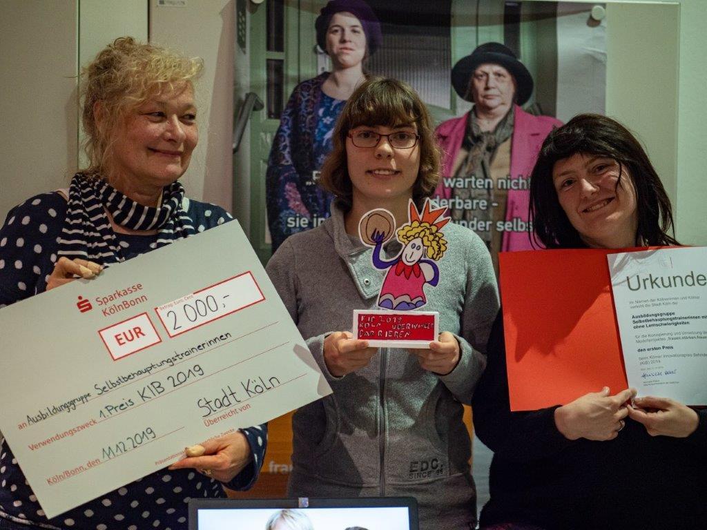 Drei Frauen halten eine Urkunde und den Preis KIB 2019 in den Händen.