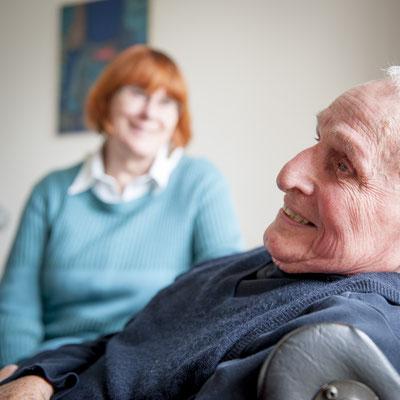 Ein älterer Mann lächelt im Vordergrund. Im Hintergrund lächelt eine Frau.