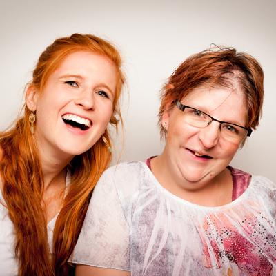 Zwei Frauen lachen und schauen in die Kamera.