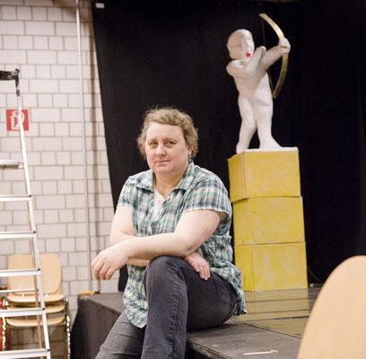 Eine Person sitzt am Rand eine Bühne.
