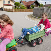 Drei Kinder spielen mit Kinderfahrzeugen auf der Strasse.