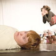 Eine Person liegt auf dem Boden. Eine andere im Hintergrund steht und hält sich die Hände vors Gesicht.