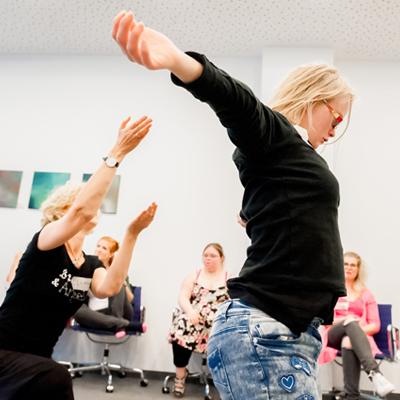 Zwei Frauen tanzen mit ausdrucksstarken Armbewegungen.