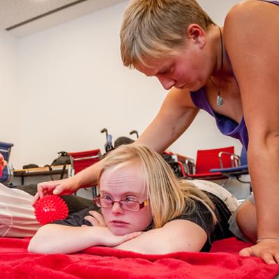 Eine Frau liegt auf einer Decke und wird von einer anderen mit einem Igelball massiert.