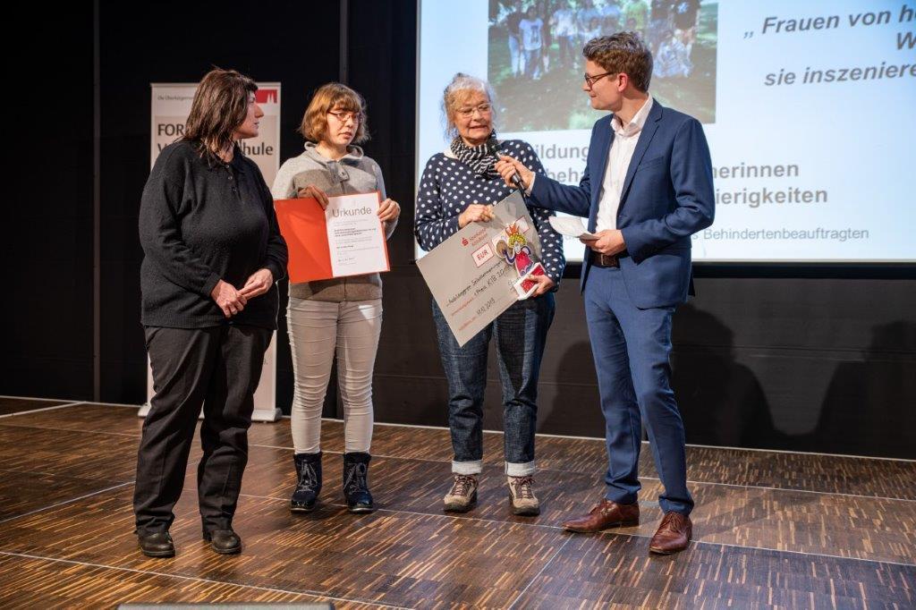 """Drei Frauen von dem Modelprojekt """"frauen stärken frauen"""" bekommen auf einer Bühne den Preis KIB 2019 überreicht."""
