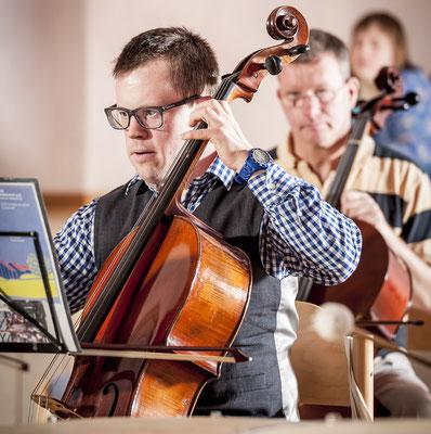 Zwei Männer spielen Cello.
