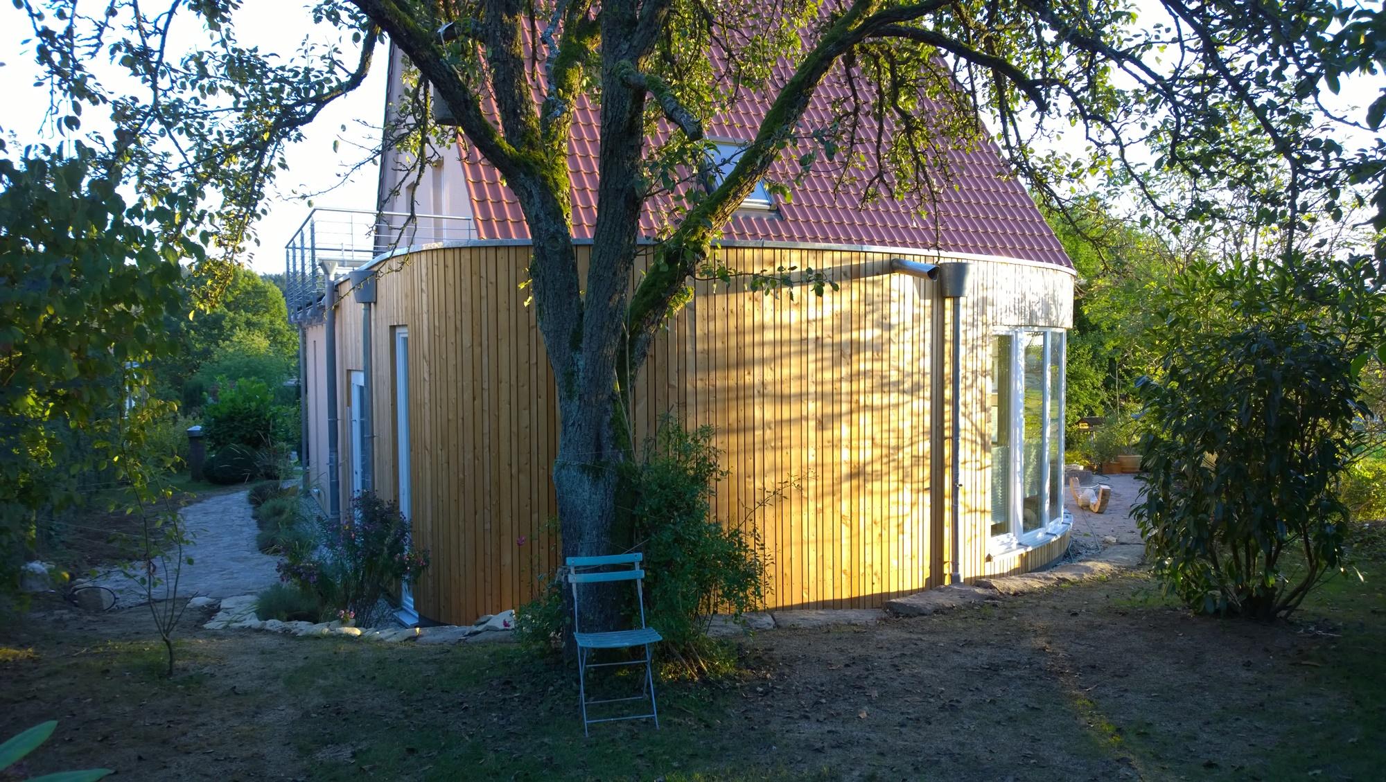 der ovale Anbau schmiegt sich perfekt in den Garten ein
