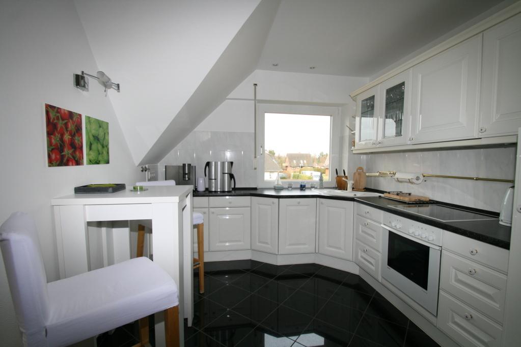 voll ausgestattete, moderne Landhausküche mit Bartisch und Barhockern