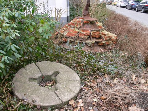 Verwilderter Garten, die Exponate versinken im Unkraut.