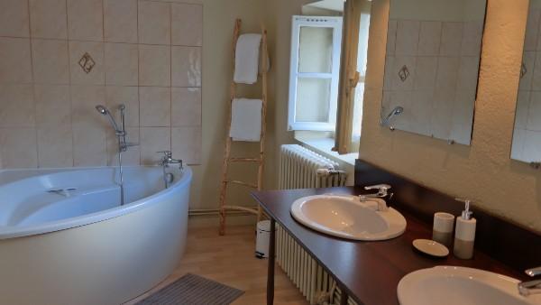 Salle de bains avec baignoire et double lavabo