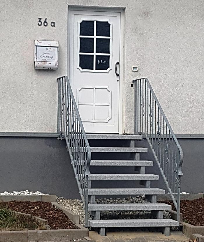 Feuerverzinkte Doppelholmtreppe mit Natursteinbelag und Integration vorhandener Geländer