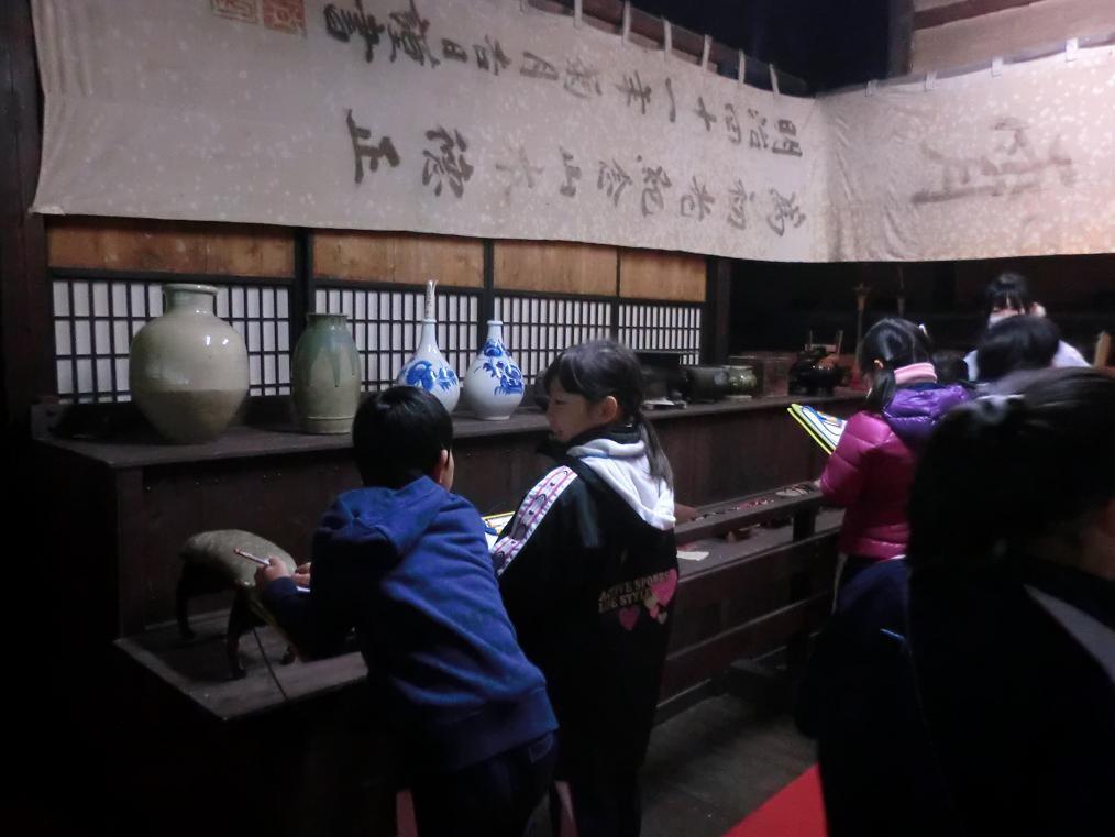 小学生の校外学習で古い農作業用具や古文書、壺等を学ぶ