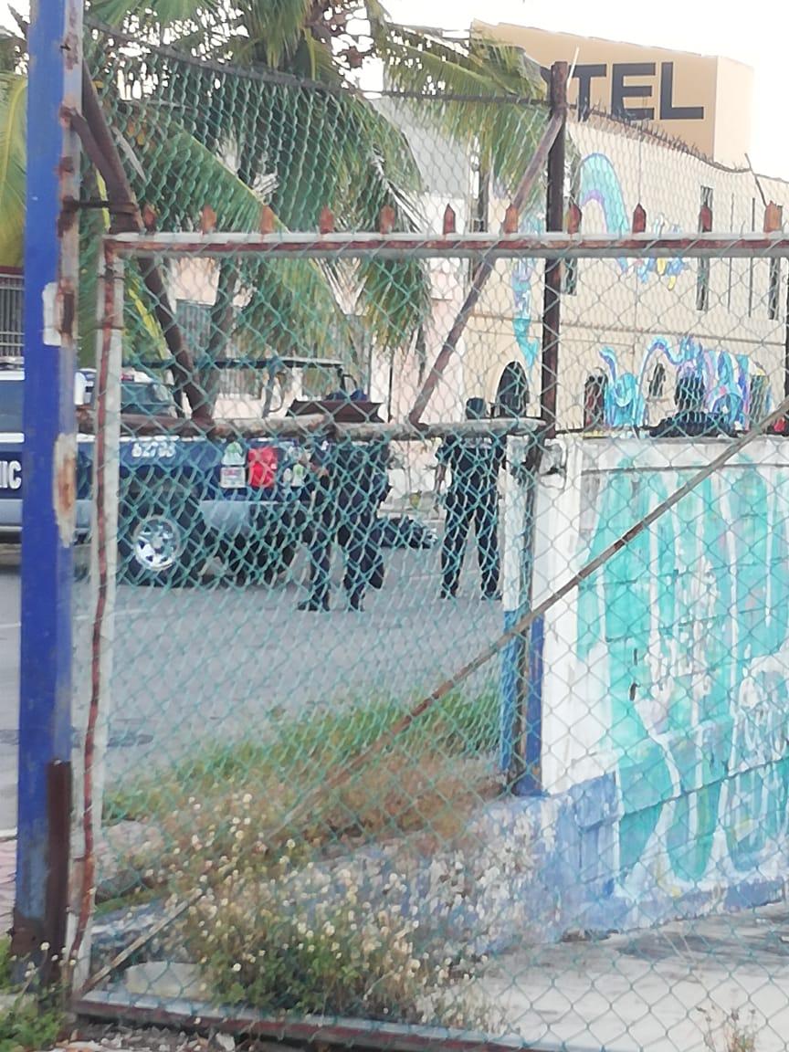 A los pies de los policías el cuerpo embolsado