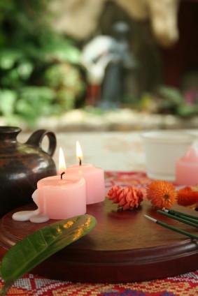 zwei brennende Kerzen, Räucherstäbchen, Teekanne und Blüten