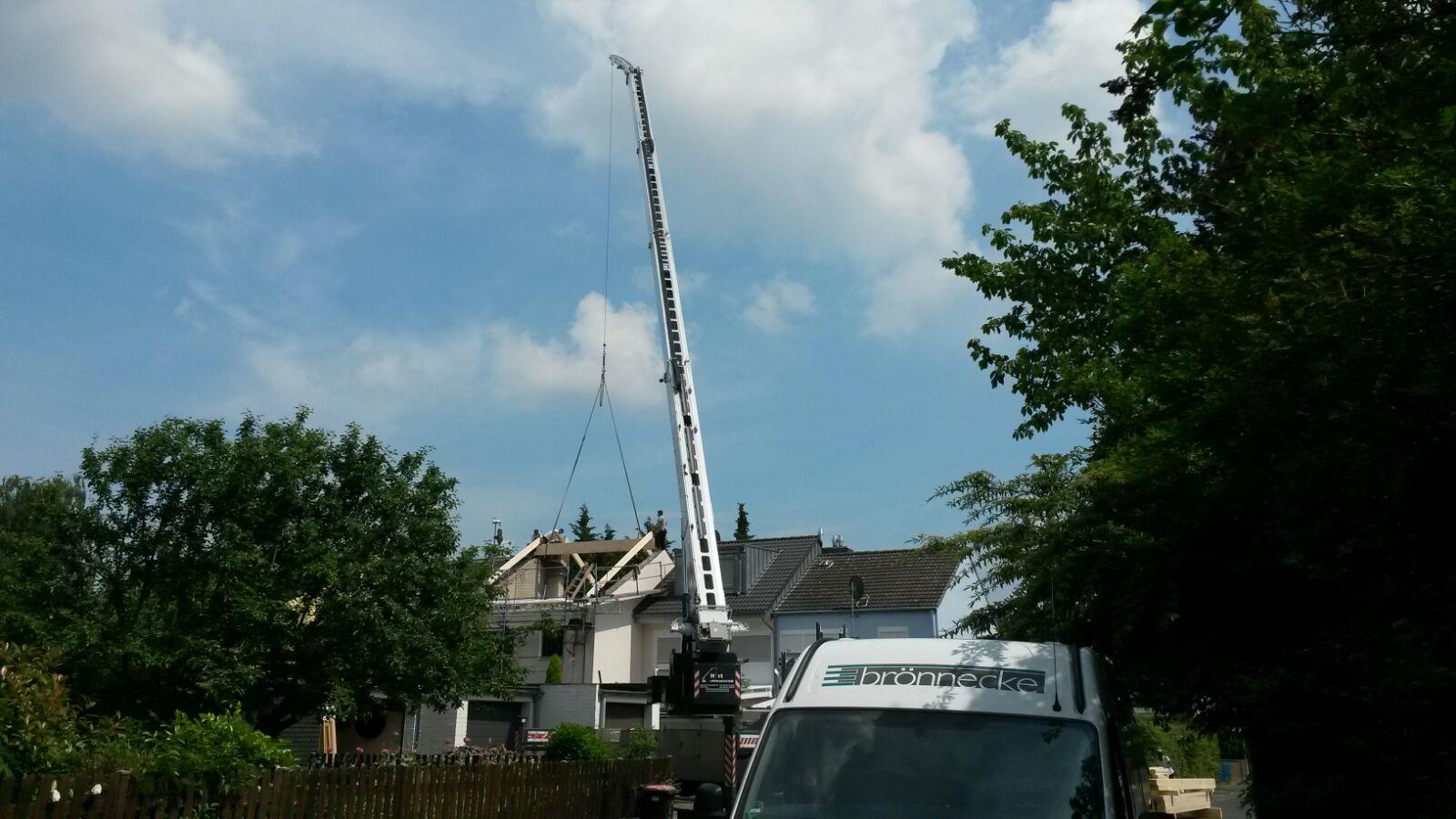 Der Kran hebt die Firstpfette auf das Dach.