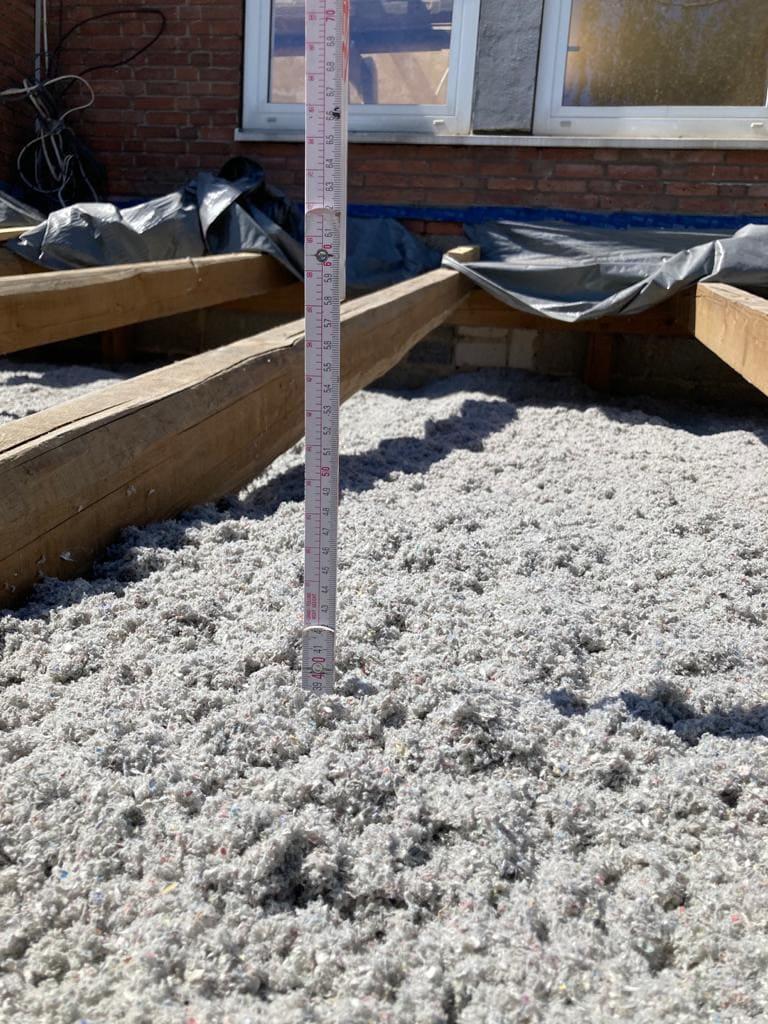Mit dem Zollstock kontrollieren wir die Dämmstärke. Hier sorgen 40 cm Zellulose für beste Wärmedämmung.