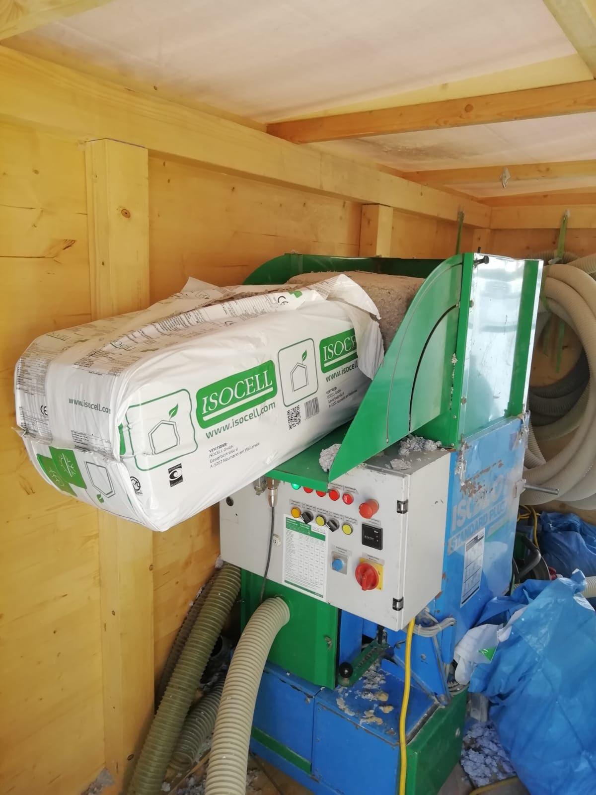 Hier wird die Zellulosedämmung in die Maschine gegeben. Dank der Umhausung aus Holz bleiben Mitarbeiter und Dämmung immer trocken.