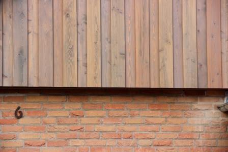 Sauberer Übergang zwischen der neuen Holzfassade und dem alten Klinker.