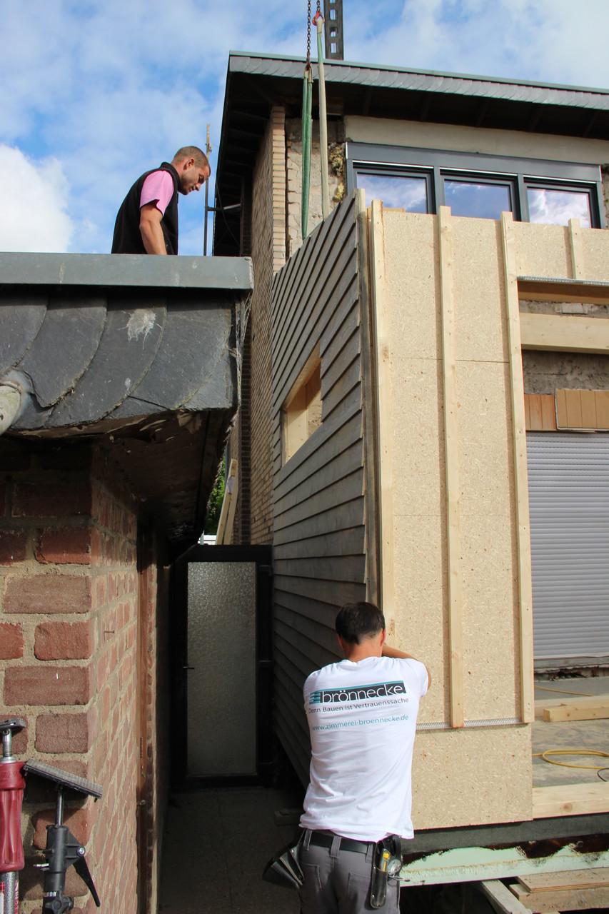 Die bereits im Vorfeld mit der Stülpschalung versehene Wand wird ausgerichtet.