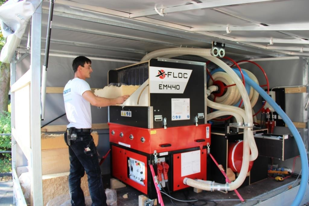 Diese Maschine zerhäckselt die Holzfaserballen und bläst sie durch den Schlauch an ihren Bestimmungsort.