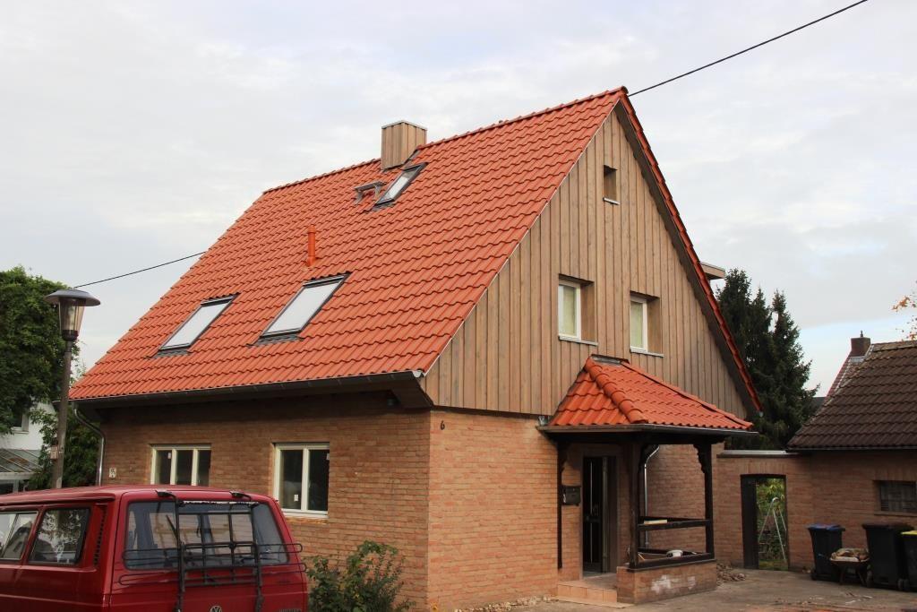 Das Haus nach der Sanierung mit neuem Dach, neuer Holzfassade und saniertem Vordach.
