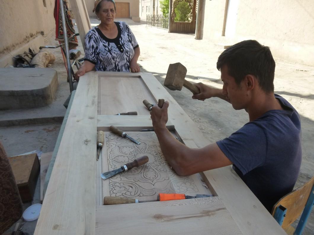 un jeune artisan sculpte une porte d'habitation privée