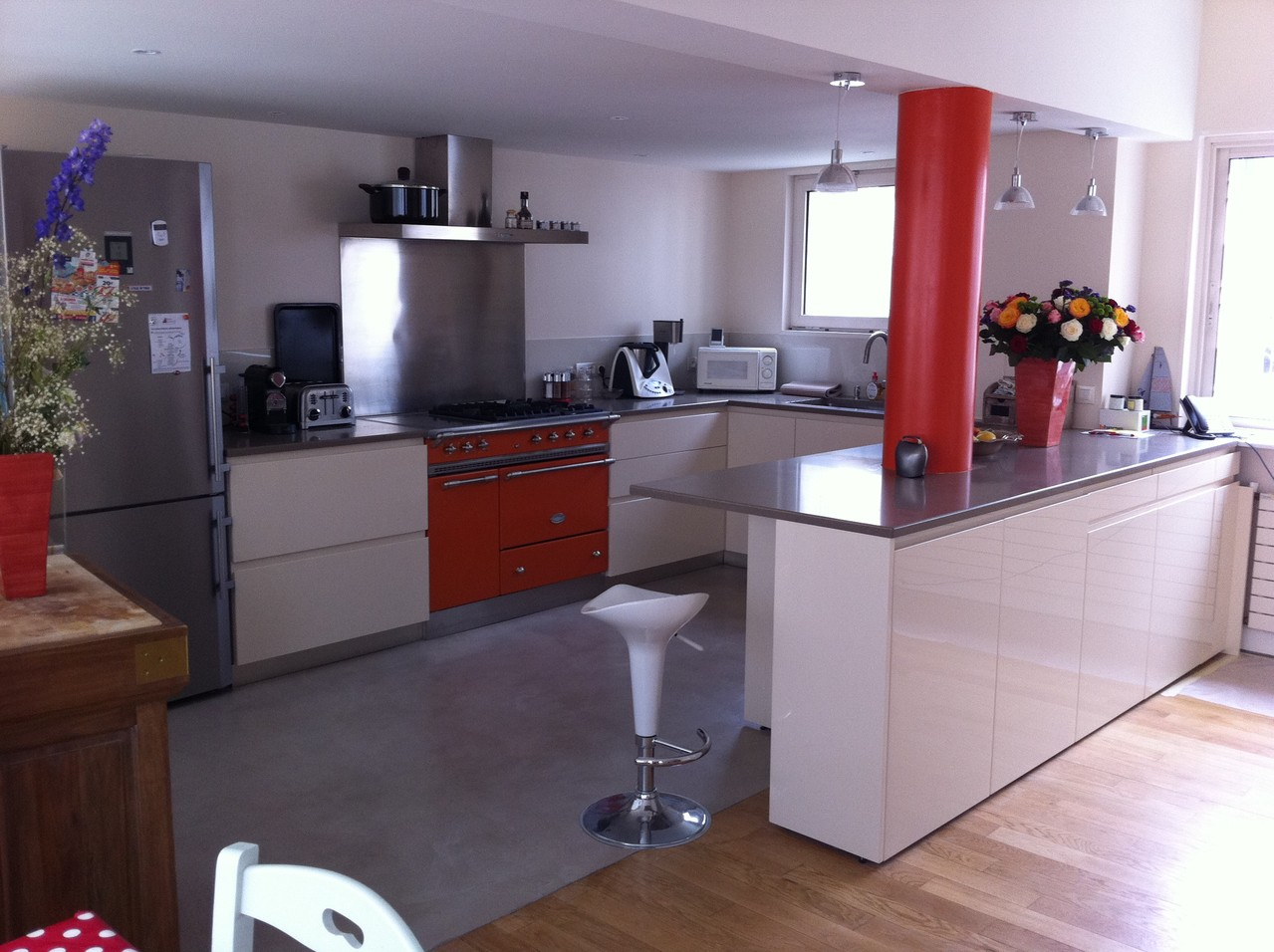 cuisine contemporaine avec ilot central et sol en béton ciré réalisée à Paris 17