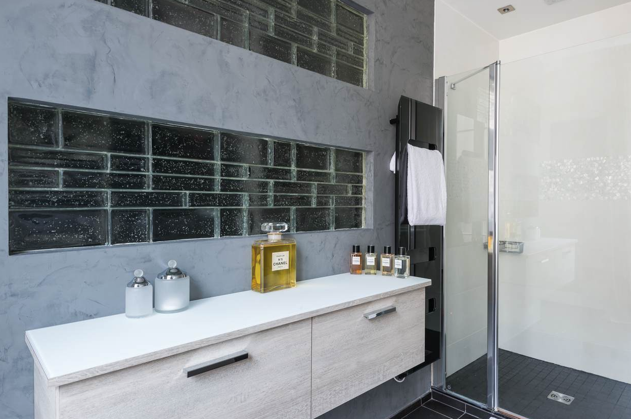 une salle de bain au mélange des matières béton ciré et pavés de verre, une harmonie de gris clairs et foncés. Rénovation complète à Paris 17ème