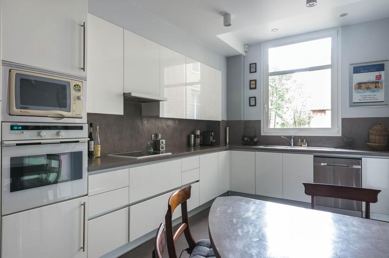 le béton ciré gris en sol, crédence et plan de travail dans un appartement familial de style haussmanien à Paris 17ème