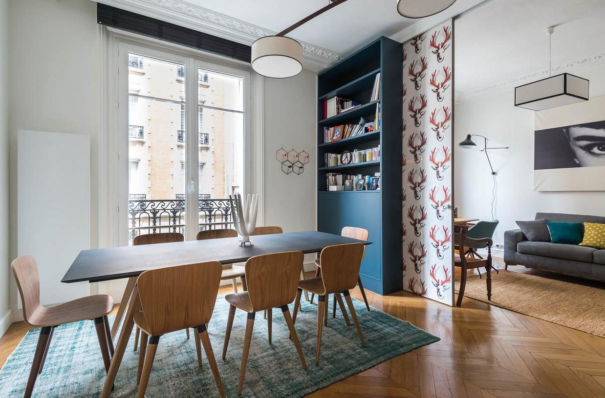 La bibliothèque sur mesure, peinte en cabine, avec portes coulissantes et ses stickers en tête de cerf. La cliente a choisi un mobilier de style scandinave et des stores à lattes bois noires.