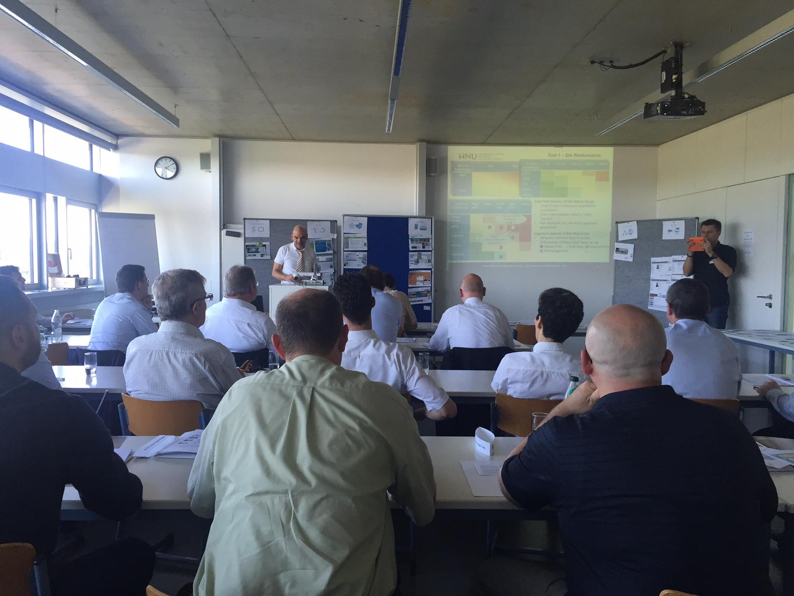 Die Teilnehmer der Veranstaltung, insbesondere zahlreiche mittelständische Unternehmer, hören dem Vortrag von Prof. Dr.-Ing. Oliver Kunze zum Thema Risk & Resource Management aufmerksam zu.
