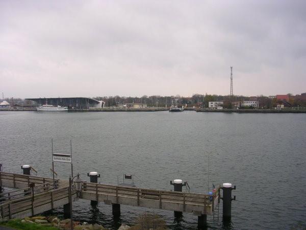 Blick vom Balkon auf den Anleger der Barkasse und auf Warnemünde im Hintergrund.